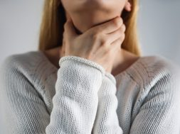 Sore throat. Woman touching the neck